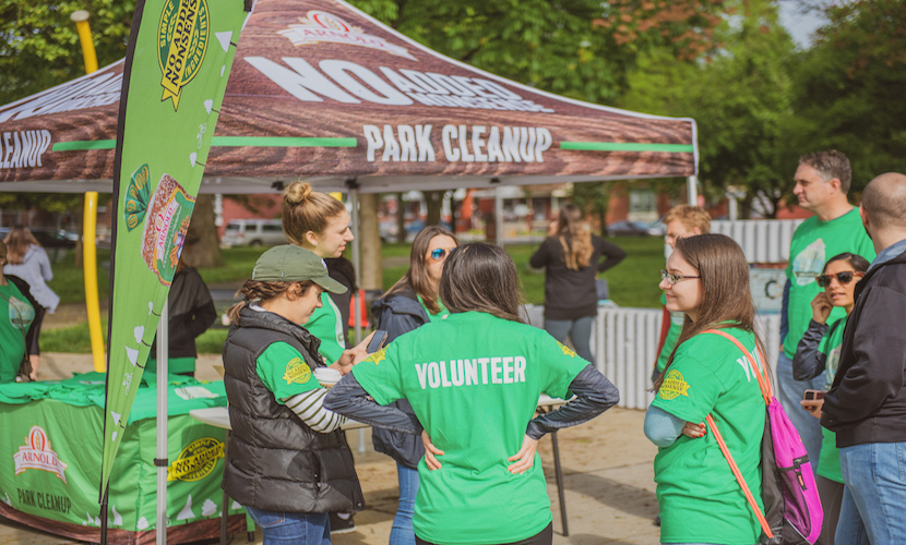 Volunteers gathering in front of park cleanup tent